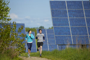 Students jog on running trails that wind through solar panels on the outskirts of Middlebury College in Vermont.