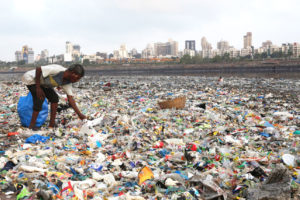 "A ""ragpicker"" on Mumbai's shoreline, which is littered with plastic waste."