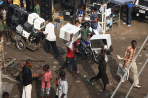 Vendors carry used air conditioners through the Alaba International Market in Lagos, Nigeria.