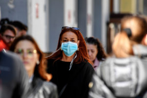 A woman wears a mask on a street in Naples, Italy this month. The country has been hit hard by the coronavirus.