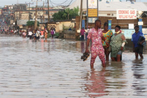 Residents wade through a road in the flooded Aboru neighborhood of Lagos, Nigeria in July.