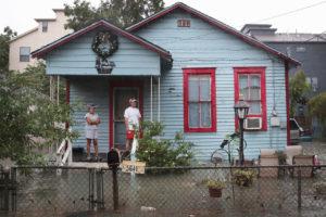 Residents of the Cottage Grove neighborhood in Houston, Texas watch as floodwaters surround their house in August 2017.