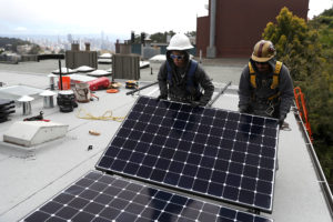 Workers install solar panels on a home in San Francisco, which has placed restrictions on the use of natural gas in new construction.