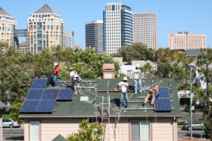 Workers put solar panels on a house near downtown Oakland under a program that uses revenue from California's cap-and-trade auctions.