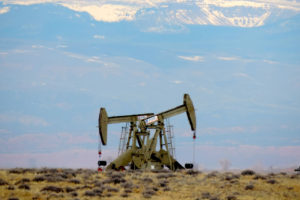 An oil pump on federal lands in northeastern Utah, with the Uinta Mountains in the background.