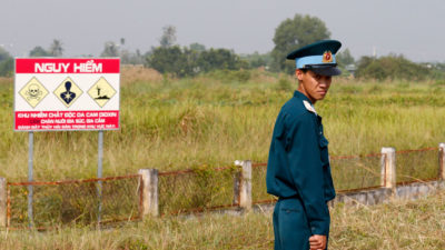 A Vietnamese soldier next to a hazardous warning sign for dioxin contamination at Bien Hoa air base last October.