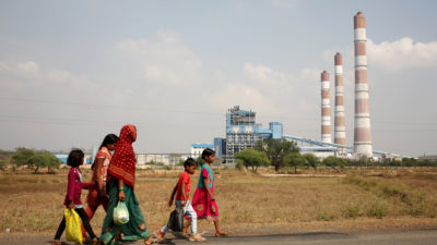 A woman and children walk past a coal-fired power plant in Chhattisgarh, India.