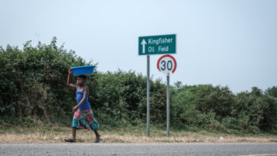 A girl walks past a sign for the Kingfisher oil field near Lake Albert in Uganda in January.
