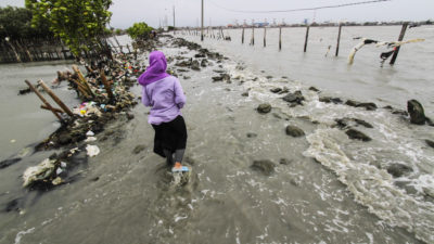 A woman walks through a broken embankment caused by rising sea levels in Central Java, Indonesia in February 2018.