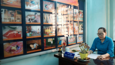 Nguyen Dao, of the Vietnamese Association of Victims of Agent Orange/Dioxin, sits next to photos of some of the more than 1,000 people with dioxin-related disabilities in Bien Hoa.
