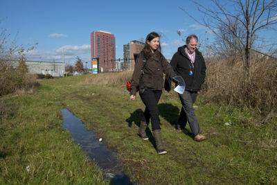 City planner Leah Kacanda and Bryan Lennon, of Wilmington's  Water Division, walk into a wetlands area that will soon be part of a new park and natural flood mitigation project.