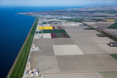 A dike, the green strip along the coast, protects flower fields and wind turbines in the northern Netherlands.