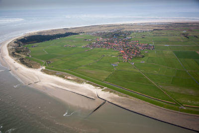 In the northern Netherlands, beach stabilization projects and a dike, just beyond the sand, protect a town.