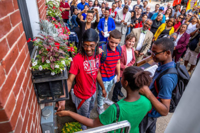 Students flip the switch to turn on rooftop solar installed on a rowhouse as part of the Solarize Philly program in 2018.