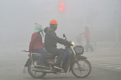 Cyclists ride through a heavy smog in the city of Weifang, in China's Shandong province, in January 2017.