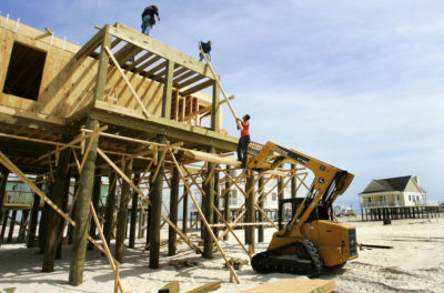 Construction workers rebuild a house destroyed by Hurricane Katrina.