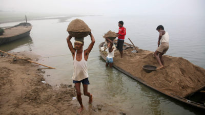Laborers transport sand from the Yamuna River in India, where a construction boom has led to indiscriminate mining of river sand.