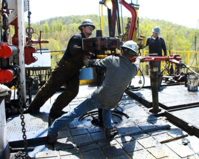 Workers move a section of well casing into place at a Chesapeake Energy natural gas site near Burlington, Pennsylvania.
