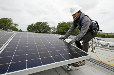 A worker installs solar panels on a house in Hayward, California amid the coronavirus outbreak.