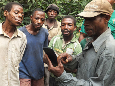 Baka community members learning how to use an app to report illegal poaching activity.