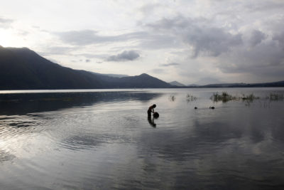 A boy collects water for his family on the shores of Samosir, an island in Lake Toba.