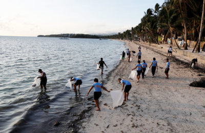Police officers collect trash on Boracay Island in the Philippines last April, days after the popular beach destination was closed to tourists to address pollution problems.