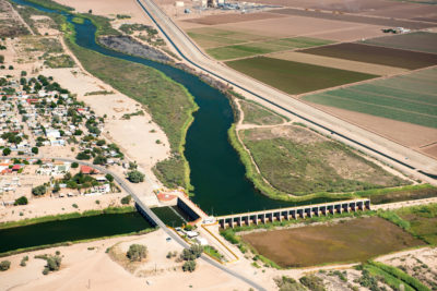 The Morelos Dam on the U.S.-Mexico border, where the Colorado's remaining water, 1.5 million acre-feet, is diverted to cities and farms in Mexico. Below the dam, the original Colorado River channel is dry.
