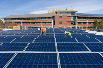 Contractors install solar panels atop Colorado State University's Braiden Hall.