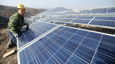 A Chinese worker installs solar panels at a solar farm in Yantai, Shandong Province.