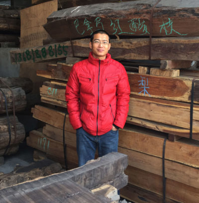 Wholesale wood dealer Chun Rong Chen stands with logs of a threatened rosewood species at his store in Zhangjiagang.