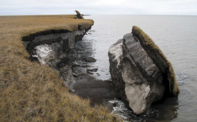 A thawing section of ice-rich permafrost falls into the sea along Drew Point, Alaska.