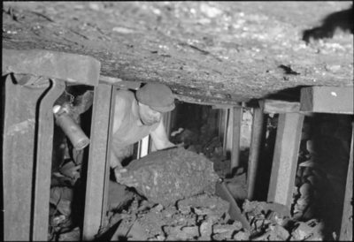 A miner lifts a lump of coal onto a conveyor belt in a mine in central England in 1944. The last of Britain's deep coal mines was closed in 2015.
