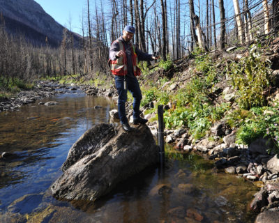 Ecologist Chris Williams examines water monitoring equipment in Waterton Lakes National Park in Alberta to track nutrient levels and sedimentation.