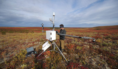 Branden Walker, a researcher from Wilfrid Laurier University, gathers data from a weather station on the tundra in the Northwest Territories.