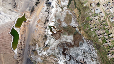 Smog surrounds the Sasol Synfuels plant in Secunda. Right: an aerial view of acidic water flowing from a coal mine in eMalahleni, Mpumalanga province in September.