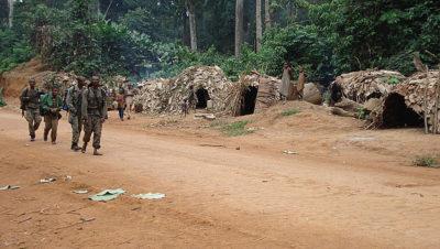 Eco-guards enter a Baka camp, preparing to conduct a raid.