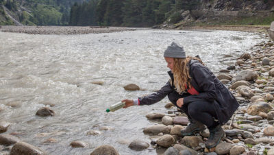 Researcher Emily Duncan releases a bottle equipped with tracking technology into the Ganges River.