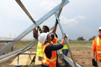 Workers receive job training while building a shared solar farm in Platteville, Colorado.