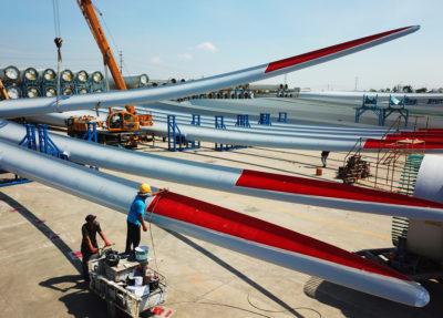 Workers examine wind turbine blades at a factory in Lianyungang, Jiangsu province, China.
