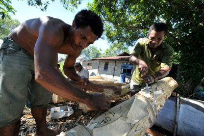 Papuan tribesmen carve a traditional wooden pole. The Trans-Papua Highway will cut through the lands of many indigenous tribes.