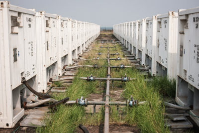 Containers of crude oil at a test drilling site in the Kingfisher oil field on the shores of Lake Albert.