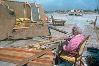 An island resident sits on the site of her former oceanfront home, which was destroyed by Hurricane Elena in 1985.