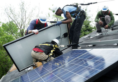 Workers install solar panels in Washington, D.C. in May 2016.