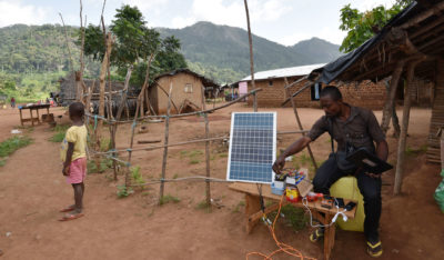 A man uses a solar panel to charge cell phones and other electric devices in a remote village in Ivory Coast that lacks access to electricity.