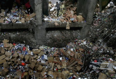A worker tosses garbage into an overflowing waste facility in Shenzhen. The city produces 300 times more trash today than it did in the 1970s.