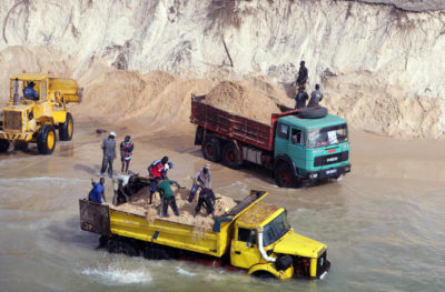 Trucks load illegally mined sea sand along beaches north of Dakar to supply Senegal's construction industry.