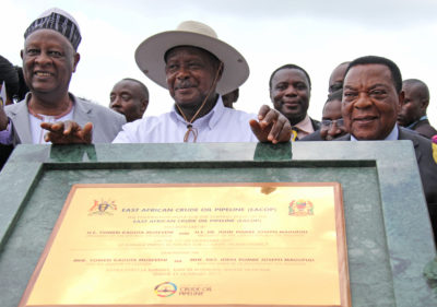 Uganda's President Yoweri Museveni, (center), with Tanzania's Minister of Foreign Affairs Augustine Mahiga (right), during a ceremony to lay the foundation stone for the East African Crude Oil Pipeline in 2017.