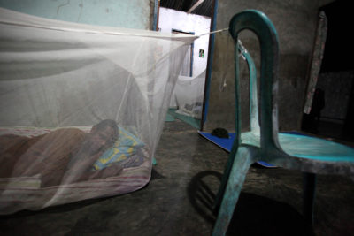 A man sleeps inside a mosquito net in his home in West Papua, Indonesia.