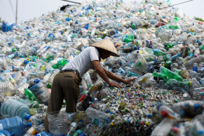 A worker sorts through plastic bottles at a waste facility in Vietnam. Other Asian countries have increased their waste imports in response to China's ban.