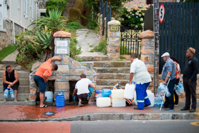 People wait to collect water from a natural spring in the Cape Town suburb of St. James in January 2018.